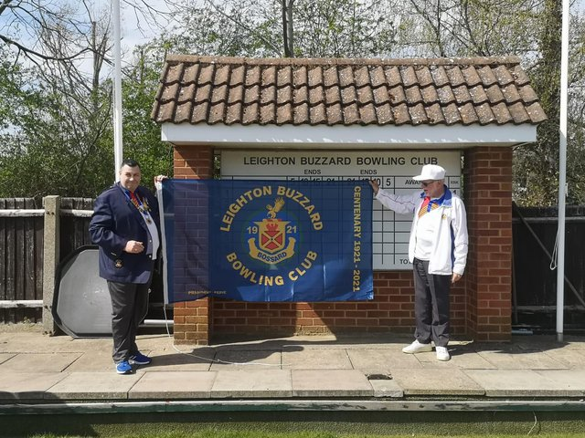 Leighton Buzzard Bowling Club President Stuart Espie and Club Chairman  Roger Clarke with the new flag to mark the centenary
